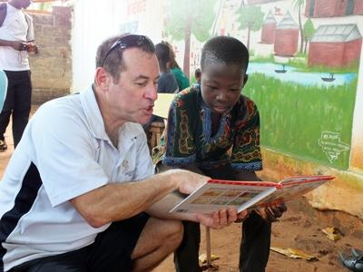 A Projects Abroad volunteer reads to children at a care placement in Togo