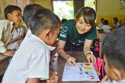 Children learn English from a teenage volunteer doing a service-learning program in Cambodia, Asia.