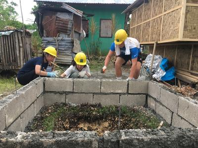Volunteers on a service and experiential learning trip to the Philippines lay bricks for a new toilet block.
