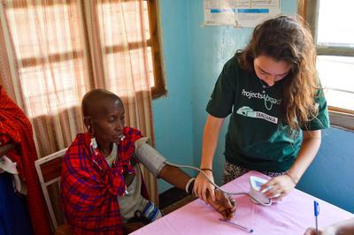 : A Tanzanian woman has her blood pressure checked by a college student on a service-learning trip to Africa.