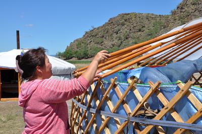 Gastmutter im Nomaden-Projekt baut eine Jurte ab