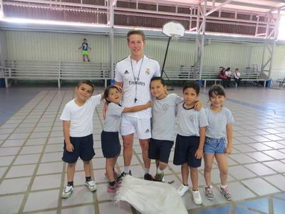 Freiwilliger mit ein paar Schülern seiner Sportklasse