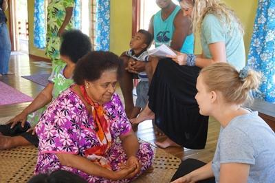Frivillig på ernæringsprojektet fortæller lokal kvinde om sund livsstil