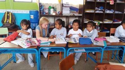 A volunteer working with young school children