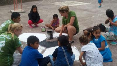 Volunteers and children painting together at a Care placement