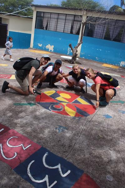 Volunteers posing next to the mural they painted