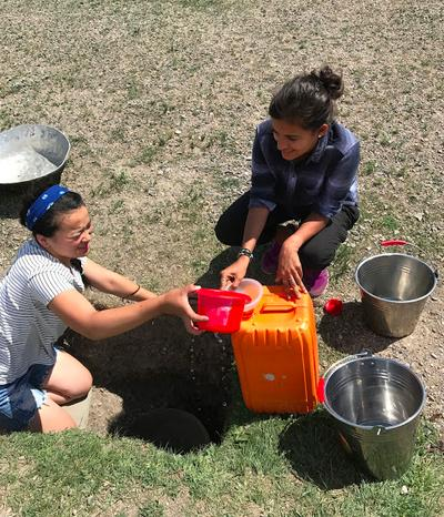 Volunteers collecting water from a hole