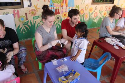 Volunteers help to dress wounds on their Public Health project