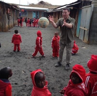 Volunteer Dean plays a ball game with students from a local school