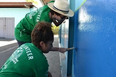 Volunteers paint a building in Jamaica