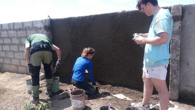 Imongen and volunteers plastering a wall during their project