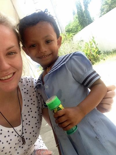 Jessica takes a photo with a local child at her project