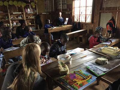 Volunteers colouring in with school children