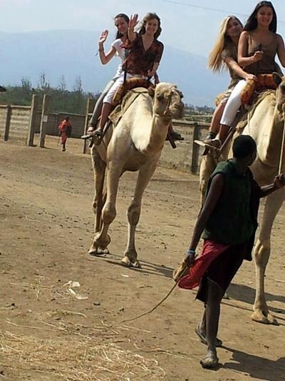 Volunteers riding camels in Tanzania