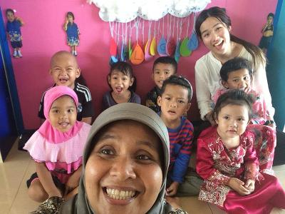 Volunteer with teacher and children in Thailand