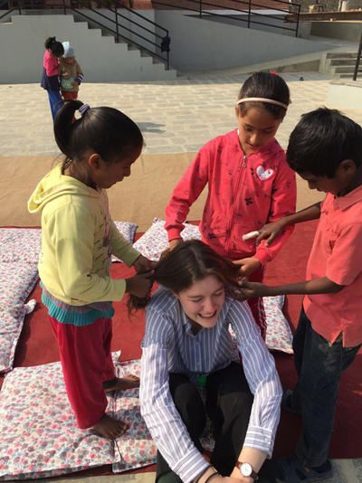 Kate getting her hair done by local children