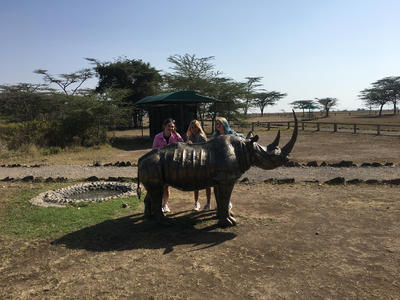 Volunteers pose with a rhino statue in Kenya
