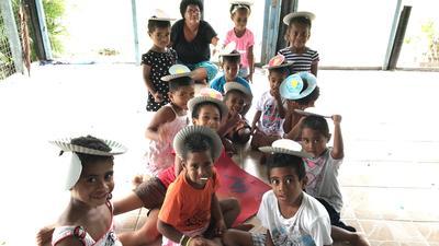 Children make hats during an art class in Fiji