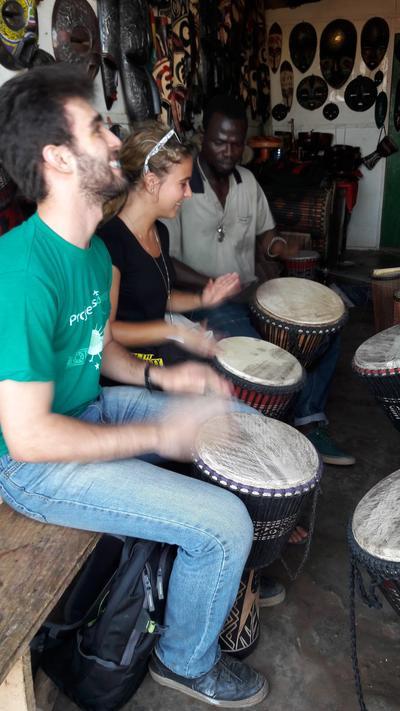 Volunteers learning to play drums in Ghana