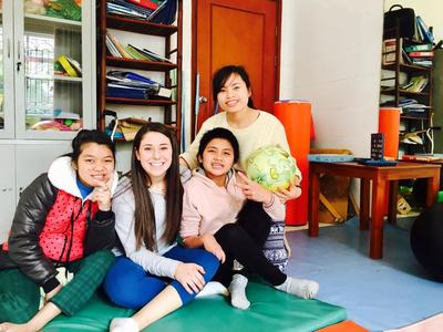 A volunteer with children and staff at a rehabilitation facility in Vietnam