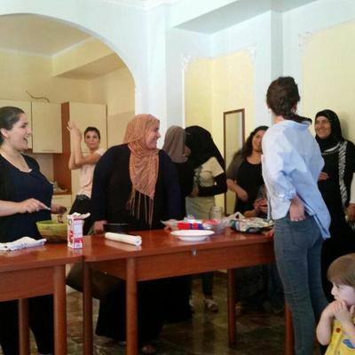 Volunteer and refugee women baking together