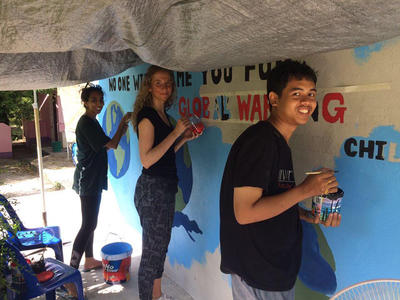Volunteers paint an educational mural