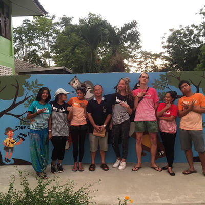 Volunteers posing in front of a mural