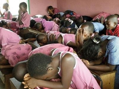 Class of students praying
