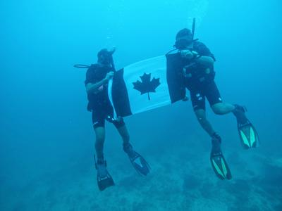 Volunteers hold up the Canadian flag during a dive