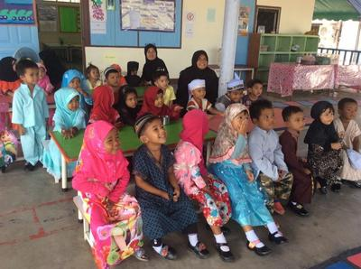 Young children listen attentively to a lesson