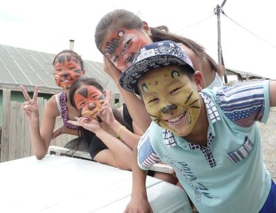 Mongolian children enjoy a face-painting activity at a day care centre