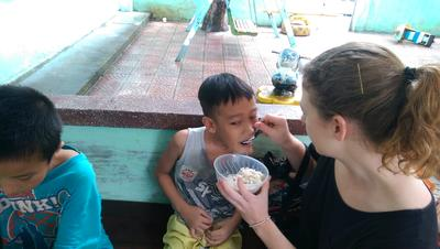 Alice feeding a child at her Physiotherapy placement