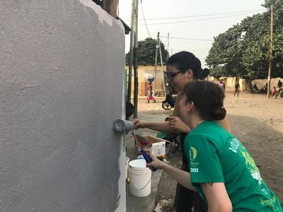 Volunteers paint a school during a community day