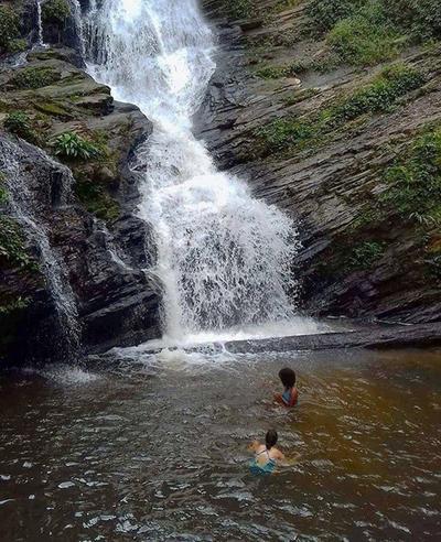Volunteers swimming beneath a waterfall in Togo