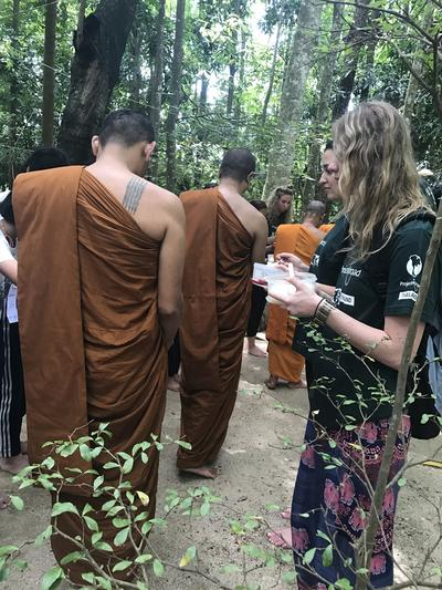 Volunteers presenting gifts to the monks in Thailand
