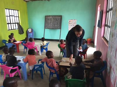 A volunteer teaches children at the Masaai school