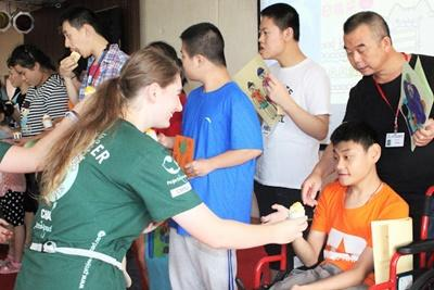 Volunteer giving a cupcake to a young disabled boy