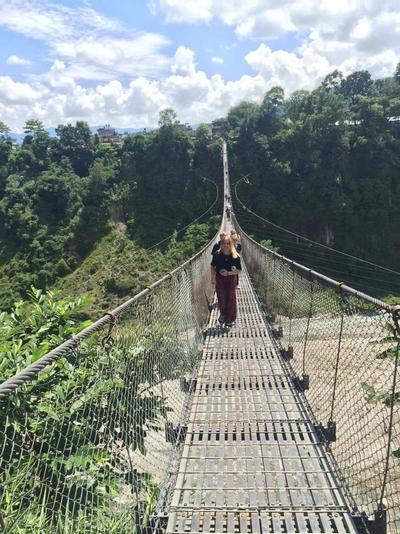 Volunteers walk across a bridge suspended over treetops
