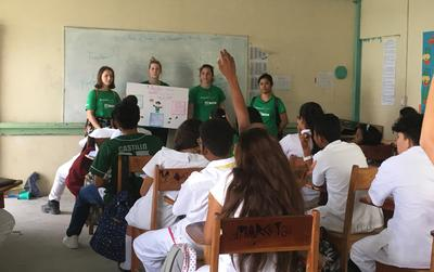 Volunteers giving a talk at a high school in Belize