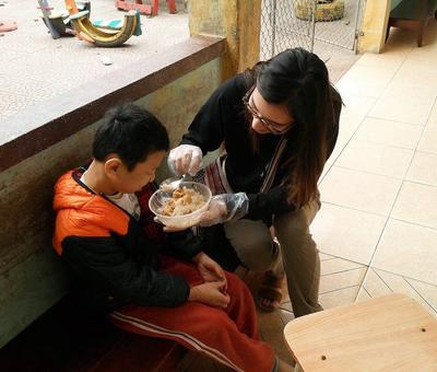 A volunteer helps a young child eat his meal