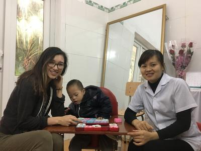 A volunteer with a young child and staff in Vietnam