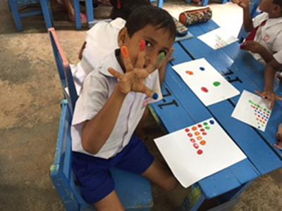 A young boy playing with finger paints in Sri Lanka