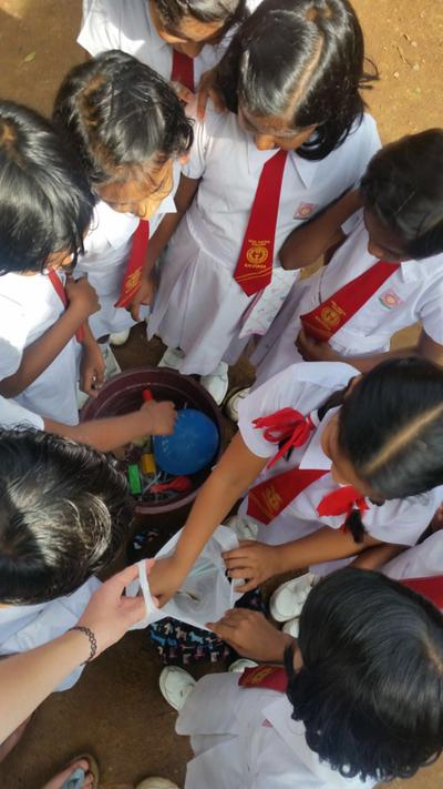 The children reaching for crayons during a game at their school