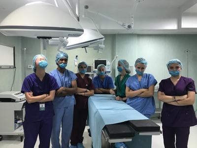 Volunteers in scrubs prepare to watch surgery