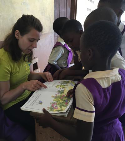 Volunteer helps children with a reading activity in Ghana