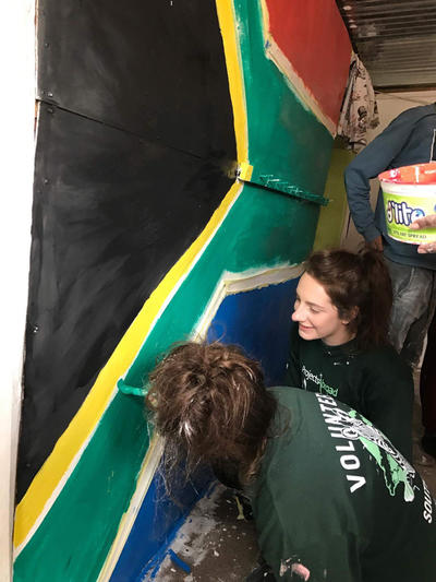 Grace and the other volunteer painting a wall mural at a day care centre