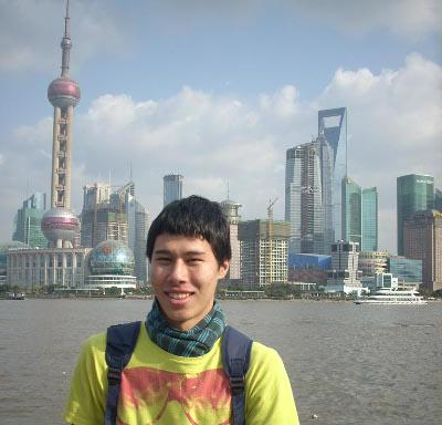 Volunteer poses in front of the Shanghai skyline while on a volunteer project in China