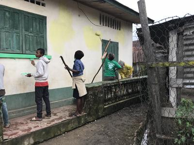 Volunteers help with painting a community hall
