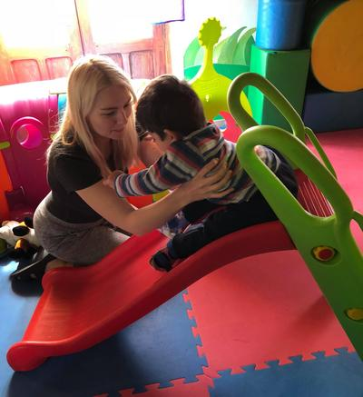 Jessica helps a child on a slide in a play room