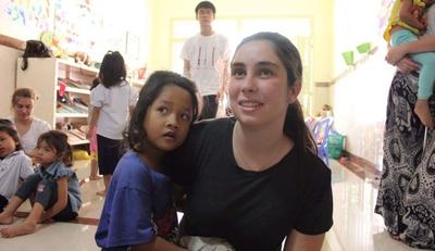 A volunteer spends time with a Cambodian child